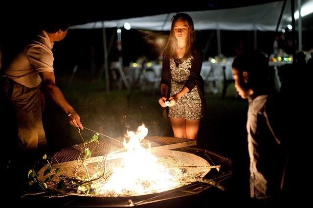 dorar marshmallows en el fuego de una hoguera